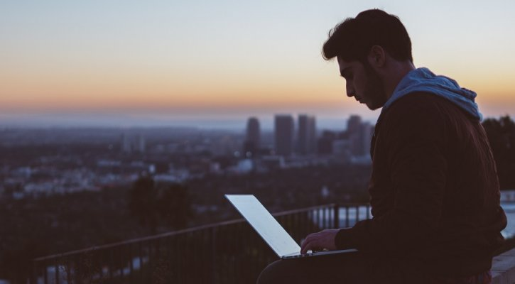 Man with laptop at sunset